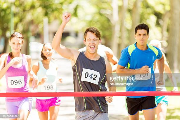 Excited Man Crossing Finish Line Of Marathon