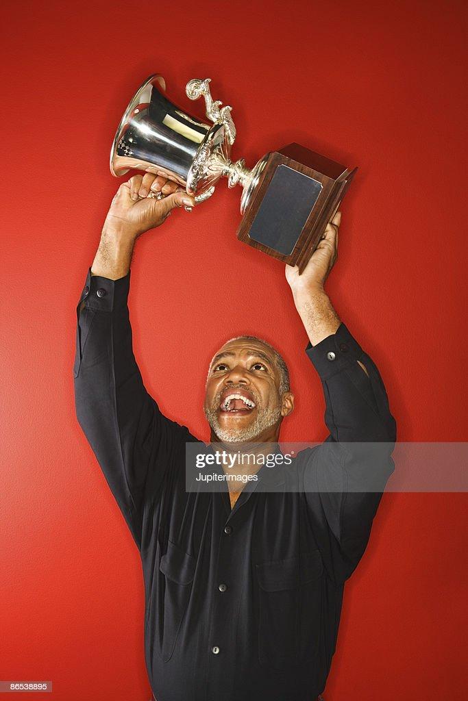 Excited man hoisting trophy