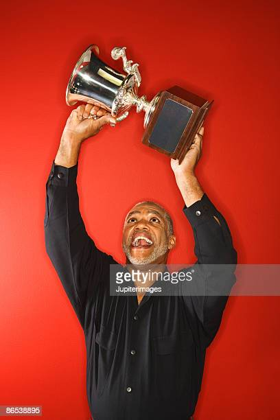 Excited man hoisting trophy