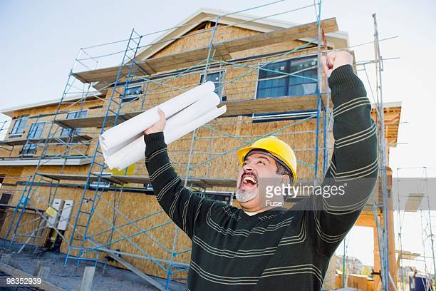 Excited man holding blueprints