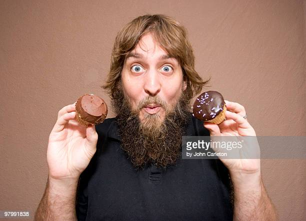 Excited man holding cupcakes