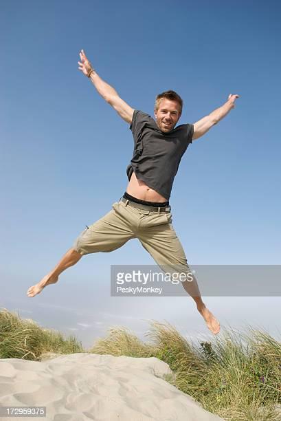 Aufgeregt Mann in T-Shirt-Jumping auf Sand Dune