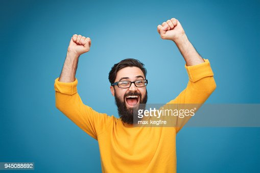 Excited man in yellow holding hands up : Stock Photo