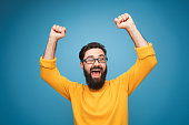 Young bearded man in eyeglasses and yellow shirt holding hands up in feeling of triumph.