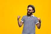 Young hipster man in sunglasses and hat holding fists up celebrating victory on orange background.