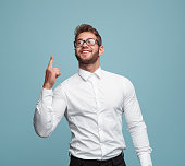 Young excited man in shirt smiling happily and pointing up having solution.