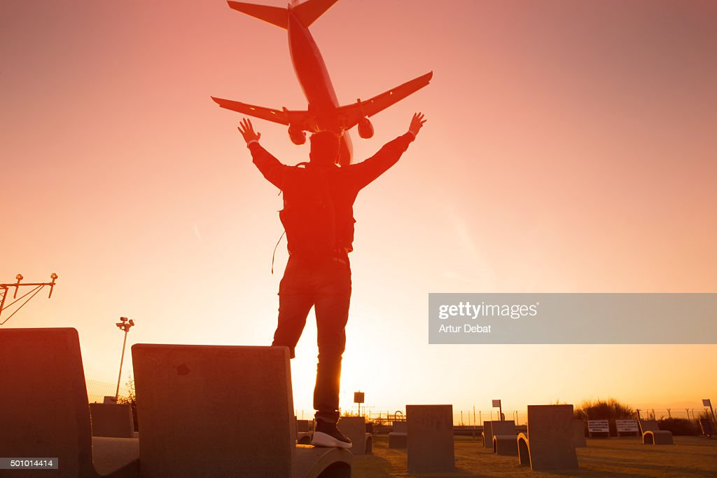 Excited man raising arms from airport viewpoint contemplating the airplanes landing.