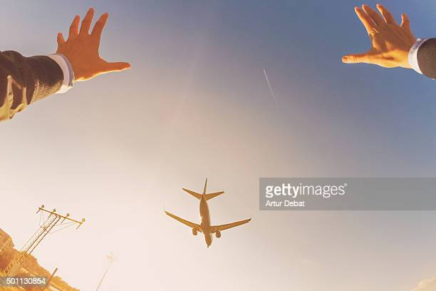 Excited man raising arms from personal point of view with airplane overhead.