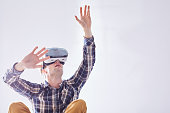 Excited man uses new technologies to have fun in virtual reality in white room