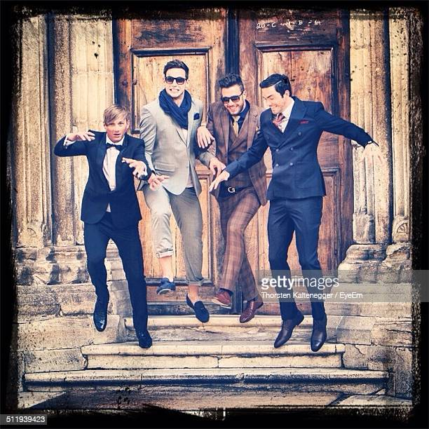 Excited men in evening wear jumping on steps