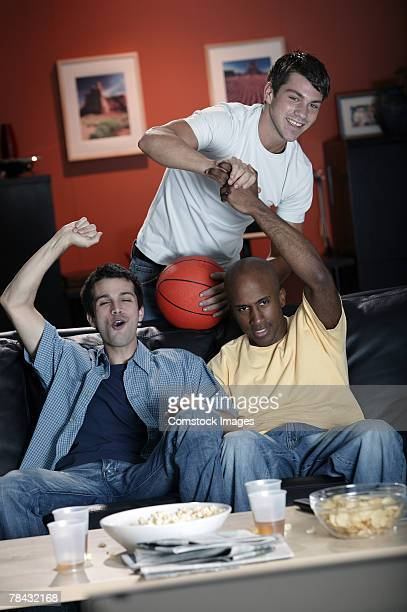 Excited men watching basketball game at home