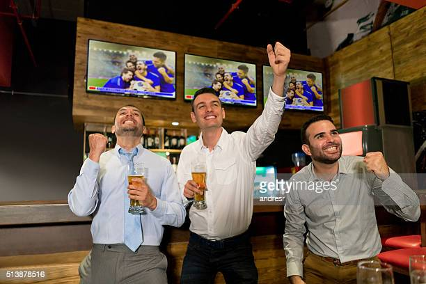 Excited men watching football at the bar