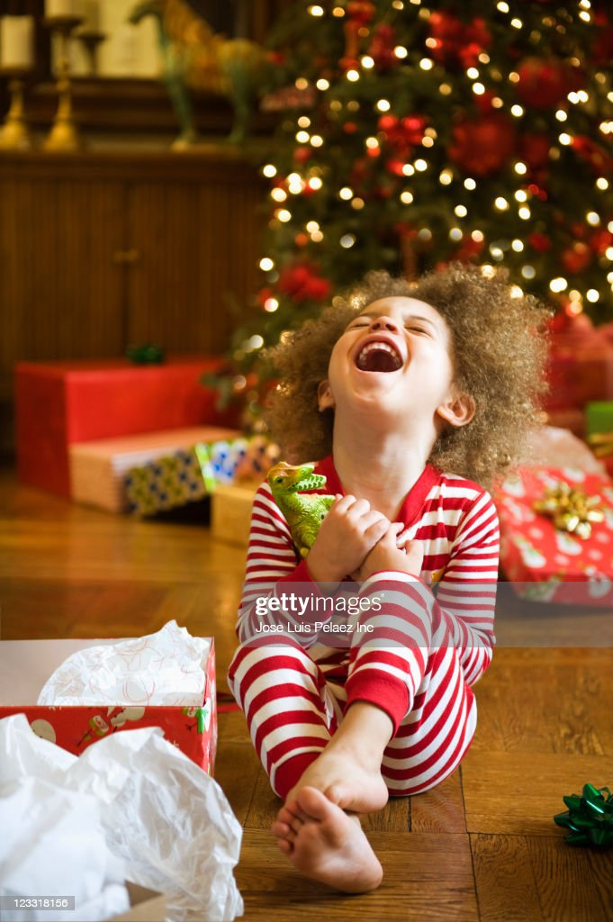 Excited mixed race boy opening Christmas gift : Stock Photo
