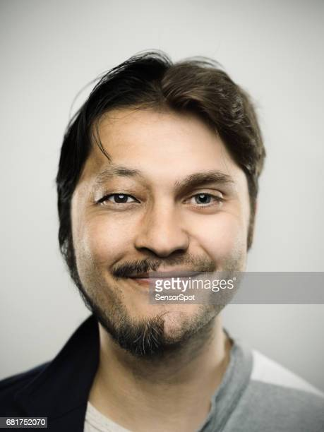 Excited mman smiling against gray background