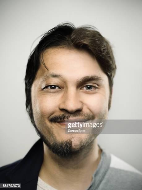 Aufgeregt Mman lächelnd vor grauem Hintergrund