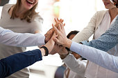 Excited happy multiracial team giving high five, celebrating good results, congratulating with success at briefing, group of employees rejoicing at achieved goal, good teamwork, collaboration, close u