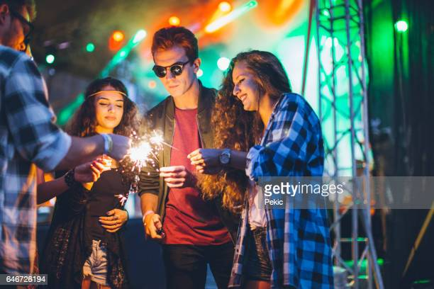 Excited music fans with sparklers at music festival
