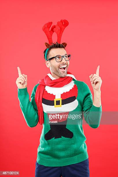 Excited nerd man in funny winter outfit against red background