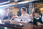 Happy excited young restaurant colleagues reaching hands with beers to toast for good job, they sitting at at bar counter