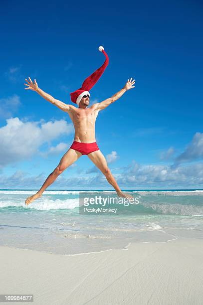 Excited Santa Hat Man Jumping for Christmas on Tropical Beach