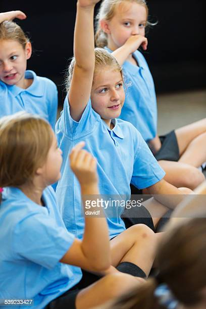 Excited School Girls in Uniform with Hands Up