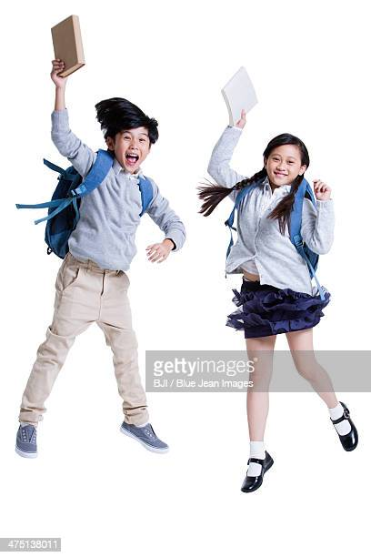 Excited schoolboy and schoolgirl jumping