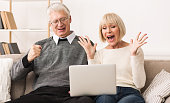 Excited senior couple celebrating victory, winning online auction bid looking at laptop