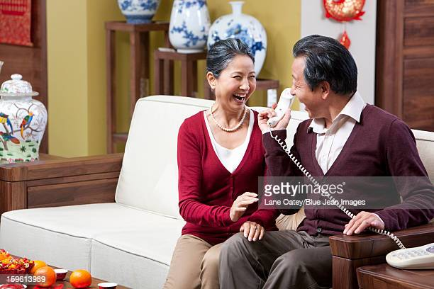 Excited senior couple on the phone during Chinese New Year
