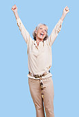 Excited senior woman in casuals cheering with arms raised against blue background