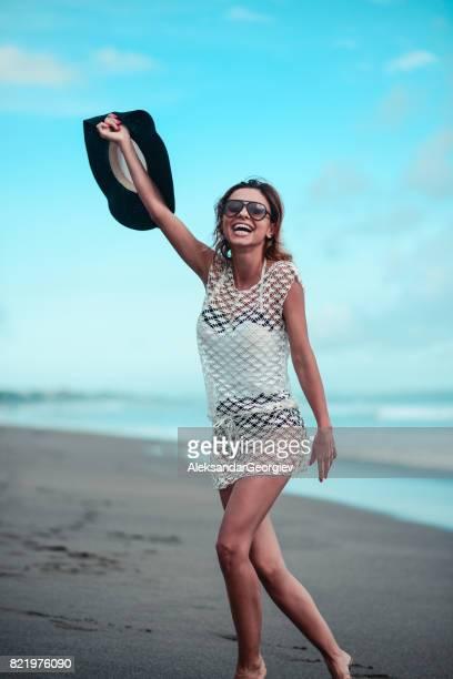 Aufgeregt, lächelnde Frau mit Sonnenbrille und Hut laufen am Strand von Ocean