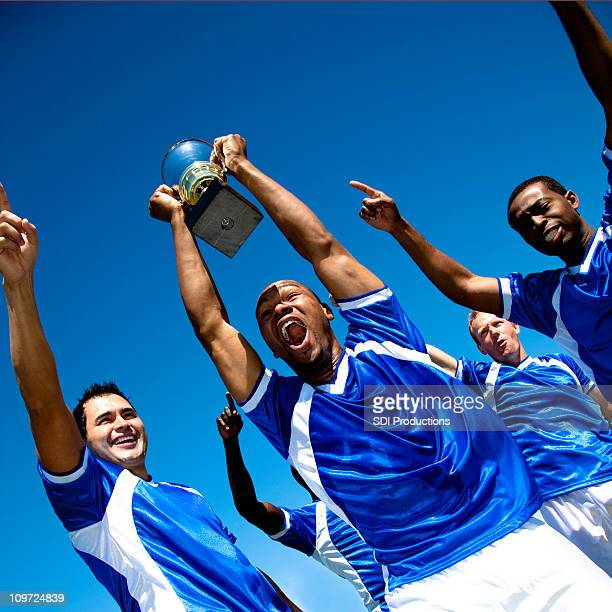 Excited Soccer Team With Trophy Celebrating Win