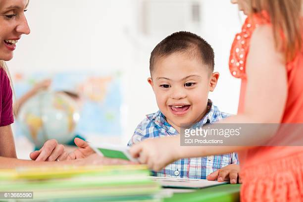 Excited special needs little boy plays in preschool class