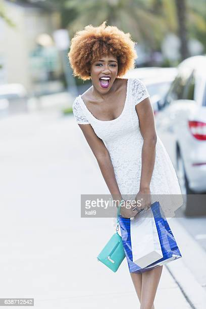 Excited stylish young black woman with shopping bags