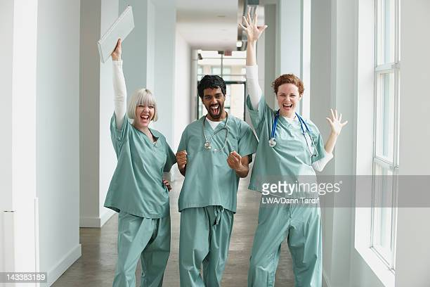 Excited surgeons standing together in hospital