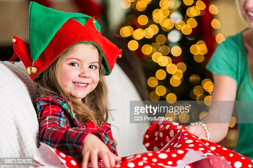 Excited sweet girl opens gift on Christmas morning
