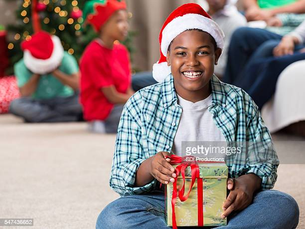 Excited teenage boy holds wrapped Christmas gift