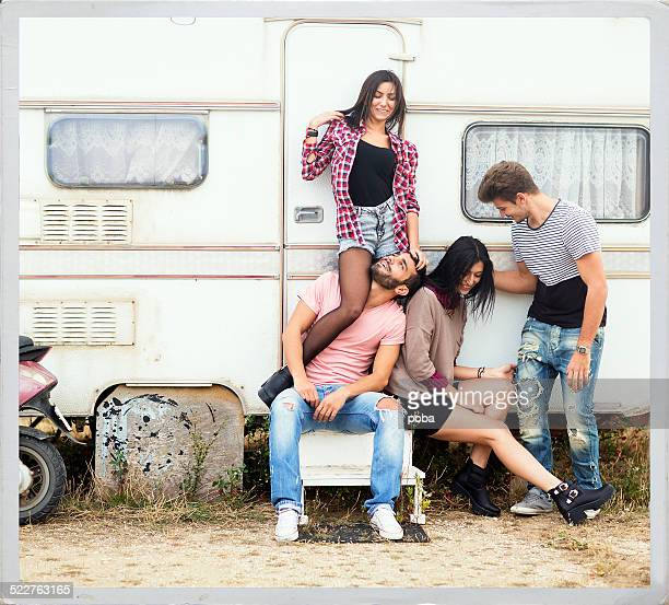 Excited teenage boys and girls posing   front of  beach trailer