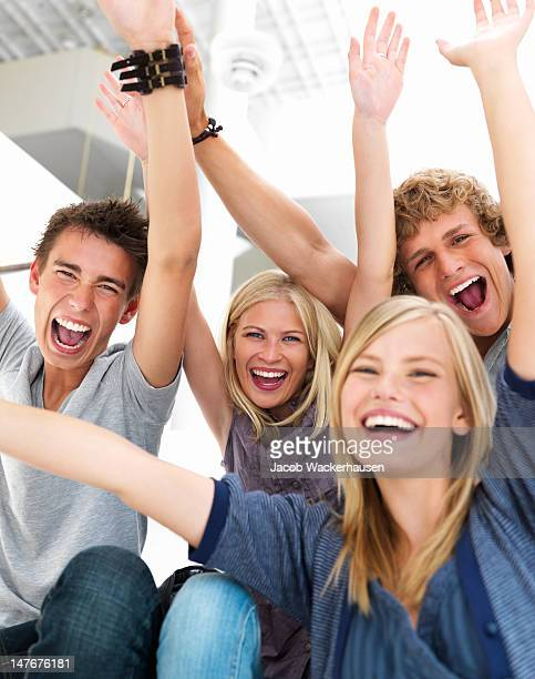 Excited teenage boys and girls shouting together with arms raised