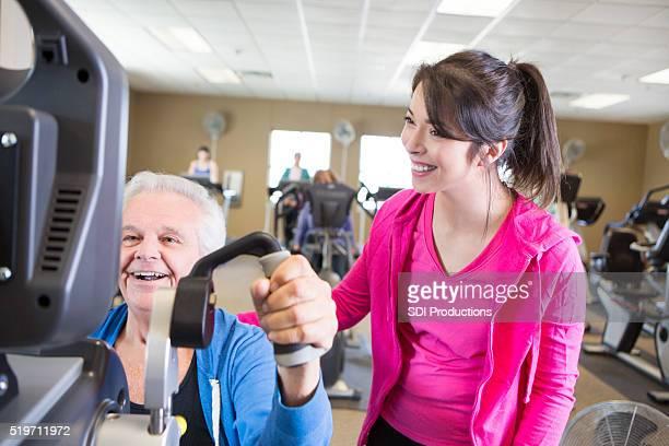 Aufgeregt Trainer encourges Alter Mann auf Fitness-Studio