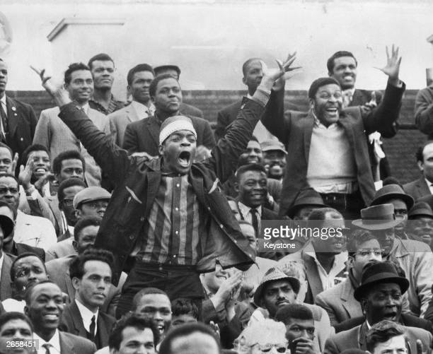 Excited West Indian supporters cheer and wave encouragement to their batsman during the test match between England and West Indies at the Oval