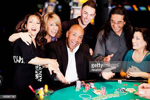 Excited winner with friends at the blackjack table