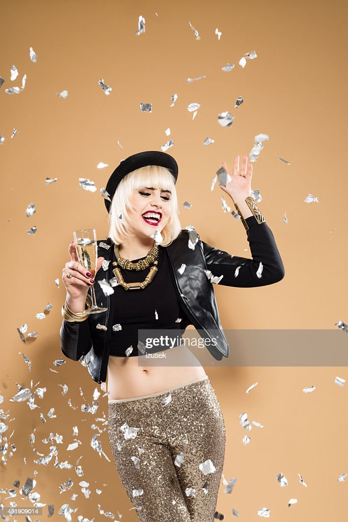 Excited woman holding a glass of champagne among confetti