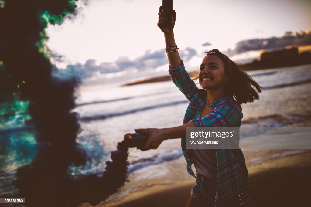 Excited woman holding smoke bombs and smiling at the beach : Foto stock