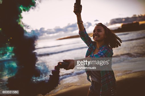 Excited woman holding smoke bombs and smiling at the beach : Stock Photo