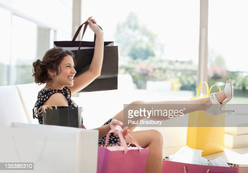 Excited woman in living room with shopping bags : Stock Photo