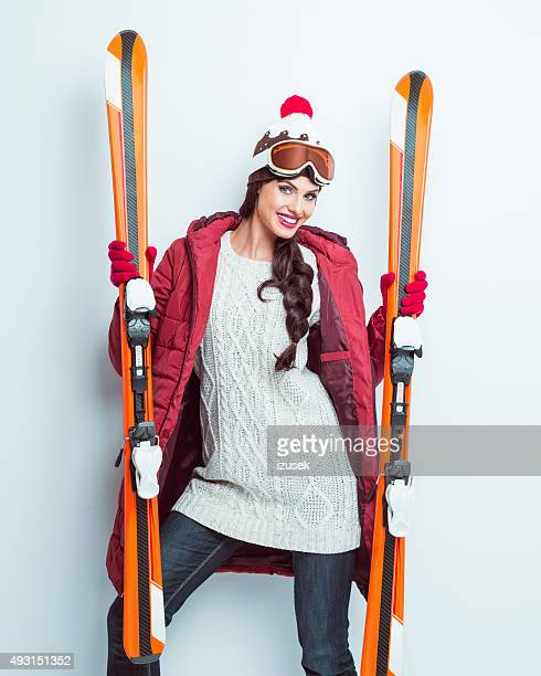 Excited woman in winter outfit holding ski