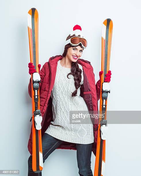 Excité femme en tenue d'hiver tenant ski