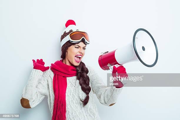 Excité femme en tenue d'hiver, criant en mégaphone