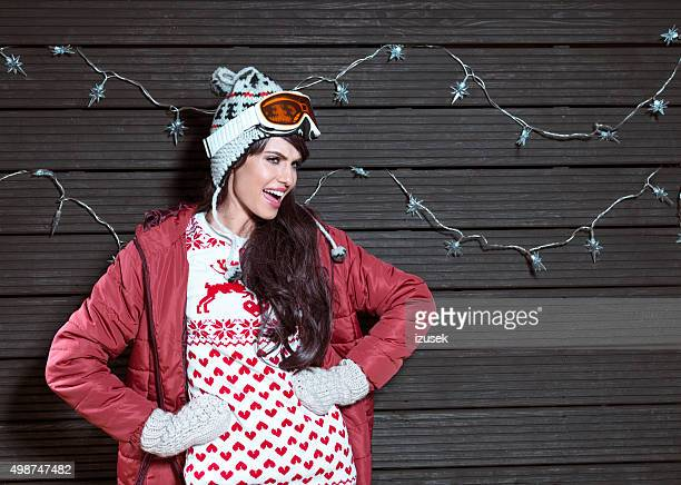 Excited woman in winter outfit, wearing puffer jacket and goggle