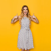 Beautiful young woman in white dotted summer dress is showing thumbs up, looking at camera and shouting. Three quarter length studio shot on yellow background.